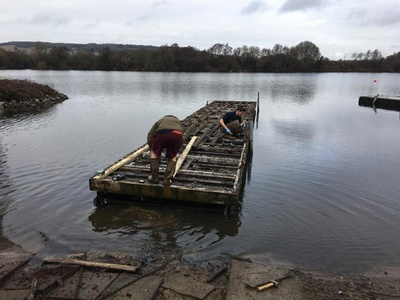 Removing old decking boards from an existing pontoon ready to replace with grey composite decking boards
